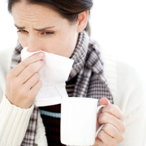 Woman Holding a Mug with a Handkerchief to Her Nose