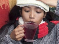 Woman in bed sick with tea, head compress
