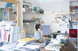 Professional seated at cluttered desk